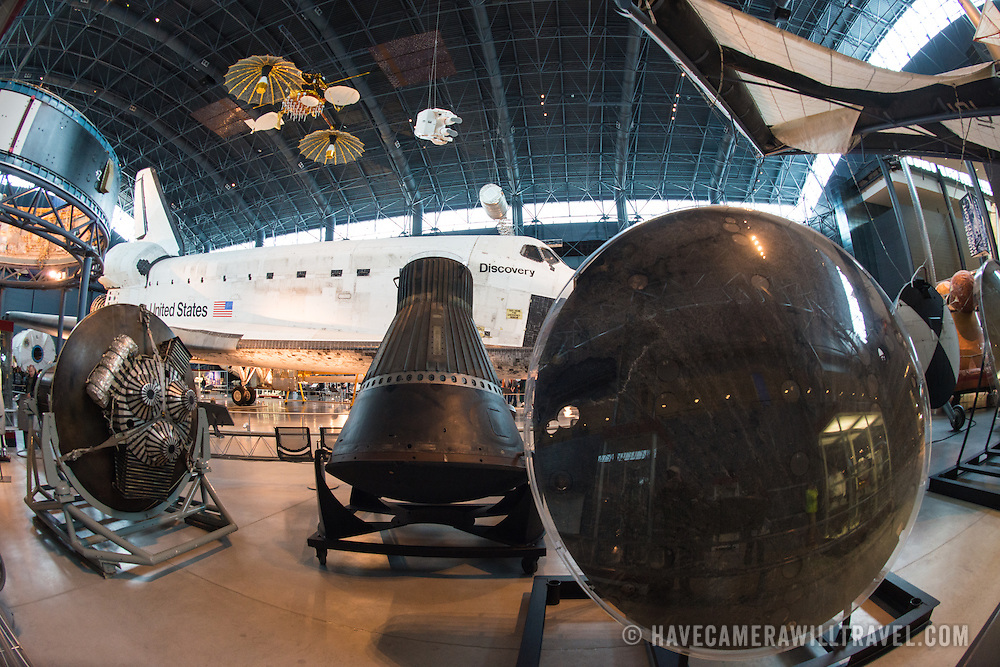 The Space Shuttle Discovery in the background, with the heat shield of a Germini capsule showing at right at the Smithsonian National Air and Space Museum's Udvar-Hazy Center. Located near Dulles Airport, the Udvar-Hazy Center is the second public facility of the Smithsonian's National Air and Space Museum. Housed in a large hangar are a multitude of planes, helicopter, rockets, and space vehicles.