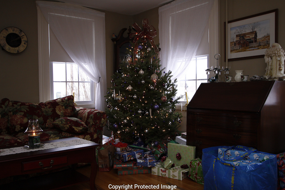 A Christmas decorated living room, presents waiting to be opened