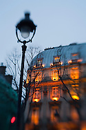 An illuminated residential building in Paris at dusk.
