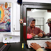 METRO--  Luis Antonio Vasquez (left) and Jesus Herrera wire money home to their families in Mexico from the DolEx wiring service at 16000 Roosevelt on Friday November 22, 2002.  ( Joshua Trujillo / Staff )