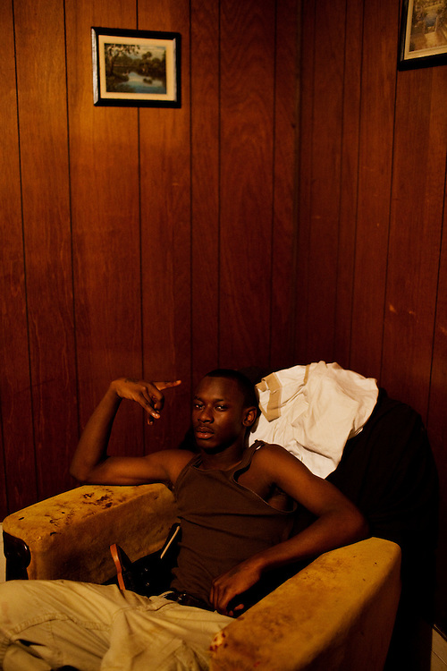 """Korwin """"Quan"""" Wilson, 17, throws up a """"BT"""" sign in his aunt Ellen Wilson's living room in the Baptist Town neighborhood of Greenwood, Mississippi on February 19, 2011."""