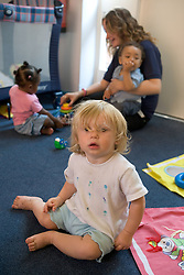 Toddler in Nursery School playroom with other children and teacher,