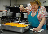 25 MARCH 2011 -- LEMAY, Mo. -- Jean Kuelker slices an industrial-sized pan of macaroni and cheese during the fish fry at St. Andrew Catholic Church in Lemay, Mo. Friday, March 25, 2011. The macaroni and cheese is one of the signature items at the fish fry, which features jack salmon, catfish, and baked or fried cod. Volunteers served more than 600 meals Friday and ran out of the macaroni and cheese, said Karen Wood, one of the parishioners who organizes the fish fry. Image © copyright 2011 Sid Hastings.