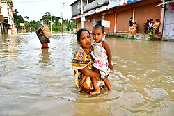 June 15, 2018 - Agartala, Tripura, India - A woman is seen carrying a small girl walking through the flooded water. Indian villagers  are leaving their houses with their children as the flood waters has entered their houses after a heavy downpour in Baldakhal village, on the outskirts of Agartala the capital of northeastern state of Tripura, India. (Credit Image: © Abhisek Saha/SOPA Images via ZUMA Wire)