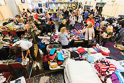 London, June 14th 2017. As fire rages through a residential tower block, Grenfell Tower, in Kensington, West London, local residents show their generosity as well-wishers pour into the Maxilla Social Club with clothing, food, water and blankets for the residents of the block who will have lost everything. PICTURED: Donated clothing is sorted by size and sex.