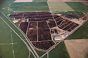 An aerial photograph of the Harris Ranch cattle feed lot, the Harris Feeding Company, in Coalinga, California. California's largest feed lot with up to 100,000 head of cattle. Coalinga, California. San Joaquin Valley. USA [[From the company: THE HARRIS FARMS GROUP OF COMPANIES. Harris Farms, Inc. is one of the nation's largest, vertically integrated family owned agribusinesses]].