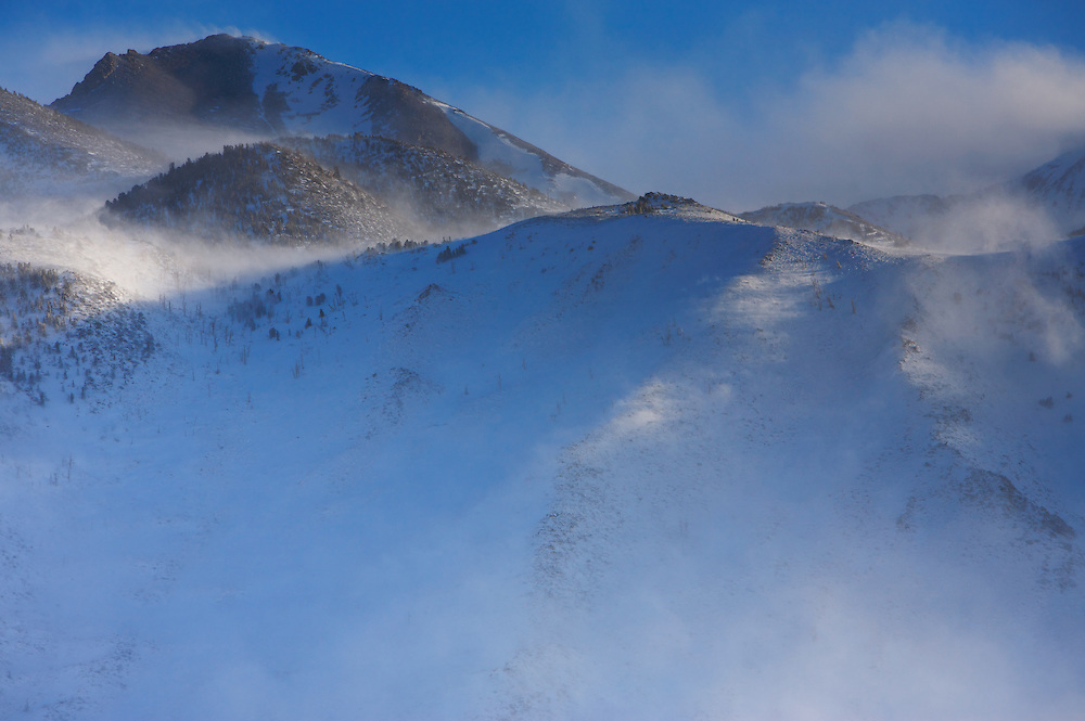 Snow blowing off mountain peaks in a strong wind near Mammoth Lakes, CA. Eastern Sierra Nevada Mountains, CA.