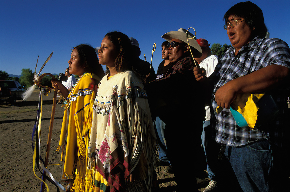 An Apache girl and her helper, both dressed in buckskin dresses, dance at her Sunrise Dance, a first menstruation rite on the San Carlos Apache Indian Reservation in Arizona, USA. The girl holds a cane that symbolises longevity. Behind her the medicine man and drummers sing and beat their drums. The Sunrise Dance is supposed to prepare the girl for adulthood and to give her a long and healthy life without material wants.The ceremony is also an enactment of the Apache creation myth and during the rites the girl 'becomes' Changing Woman, a mythical female figure, and comes into possession of her healing powers.