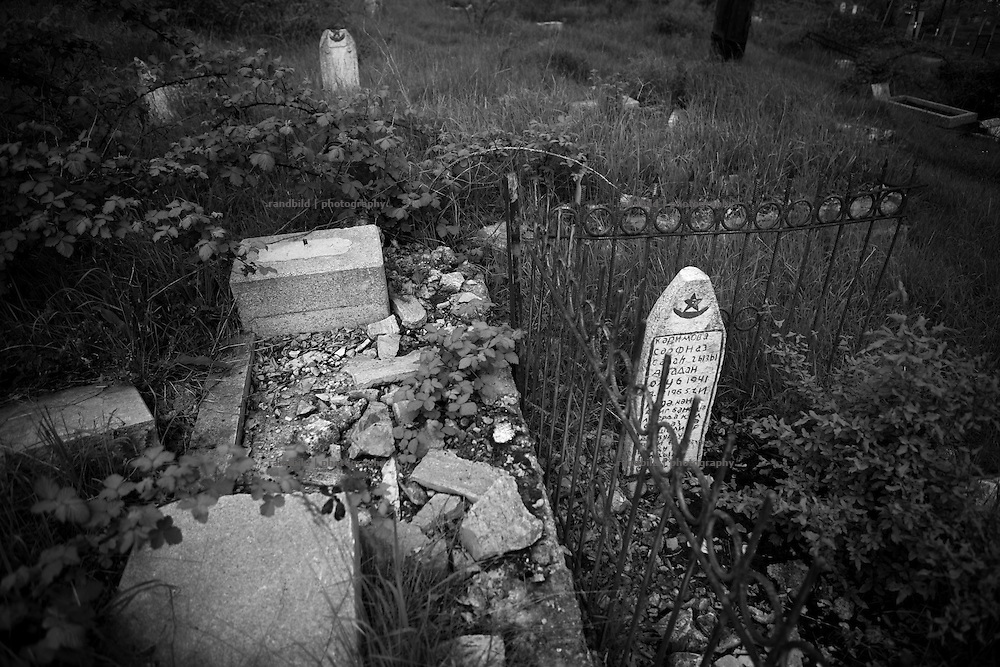 "Old and ruined asri (muslim) cemetery in Shushi. This image is part of the photoproject ""The Twentieth Spring"", a portrait of caucasian town Shushi 20 years after its so called ""Liberation"" by armenian fighters. In its more than two centuries old history Shushi was ruled by different powers like armeniens, persians, russian or aseris. In 1991 a fierce battle for Karabakhs independence from Azerbaijan began. During the breakdown of Sowjet Union armenians didn´t want to stay within the Republic of Azerbaijan anymore. 1992 armenians manage to takeover ""ancient armenian Shushi"" and pushed out remained aseris forces which had operate a rocket base there. Since then Shushi became an ""armenian town"" again. Today, 20 yeras after statement of Karabakhs independence Shushi tries to find it´s opportunities for it´s future. The less populated town is still affected by devastation and ruins by it´s violent history. Life is mostly a daily struggle for the inhabitants to get expenses covered, caused by a lack of jobs and almost no perspective for a sustainable economic development. Shushi depends on donations by diaspora armenians. On the other hand those donations have made it possible to rebuild a cultural centre, recover new asphalt roads and other infrastructure. 20 years after Shushis fall into armenian hands Babies get born and people won´t never be under aseris rule again. The bloody early 1990´s civil war has moved into the trenches of the frontline 20 kilometer away from Shushi where it stuck since 1994. The karabakh conflict is still not solved and could turn to an open war every day. Nonetheless life goes on on the south caucasian rocky tip above mountainious region of Karabakh where Shushi enthrones ever since centuries."