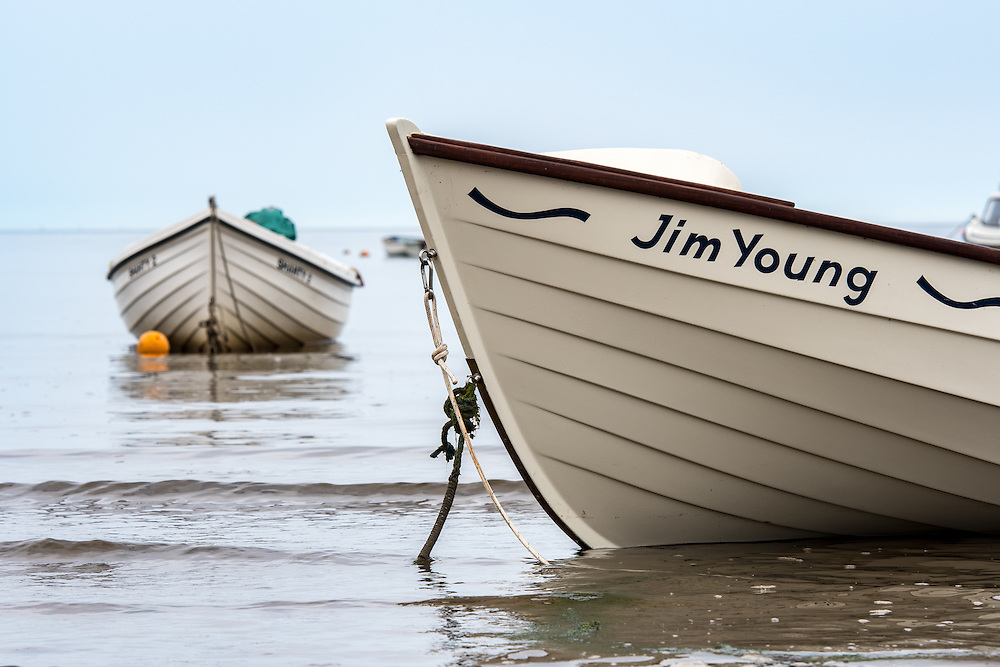 UK, England, Yorkshire - Boats in the water on a beach right outside the small fishing village called Robin Hood's Bay, located on the coast of North Yorkshire, England.
