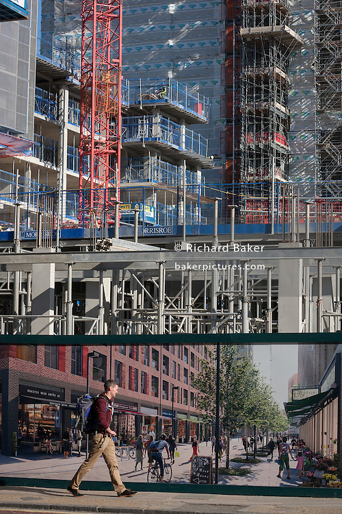 A south Londoner walks past a regeneration project hoarding at Elephant Park, at Elephant & Castle, London borough of Southwark. Southwark Council's development partner, Lendlease is regenerating over 28 acres across three sites at the heart of Elephant & Castle, in what is the latest major regeneration opportunity in zone 1 London. The vision for the £1.5 billion regeneration is to build on the area's strengths and vibrant character in order to re-establish Elephant & Castle as one of London's most flourishing urban quarters. The Elephant & Castle regeneration is of a scale rarely seen in central London and includes almost 3,000 new homes, plus office, retail, community, leisure and restaurant space.