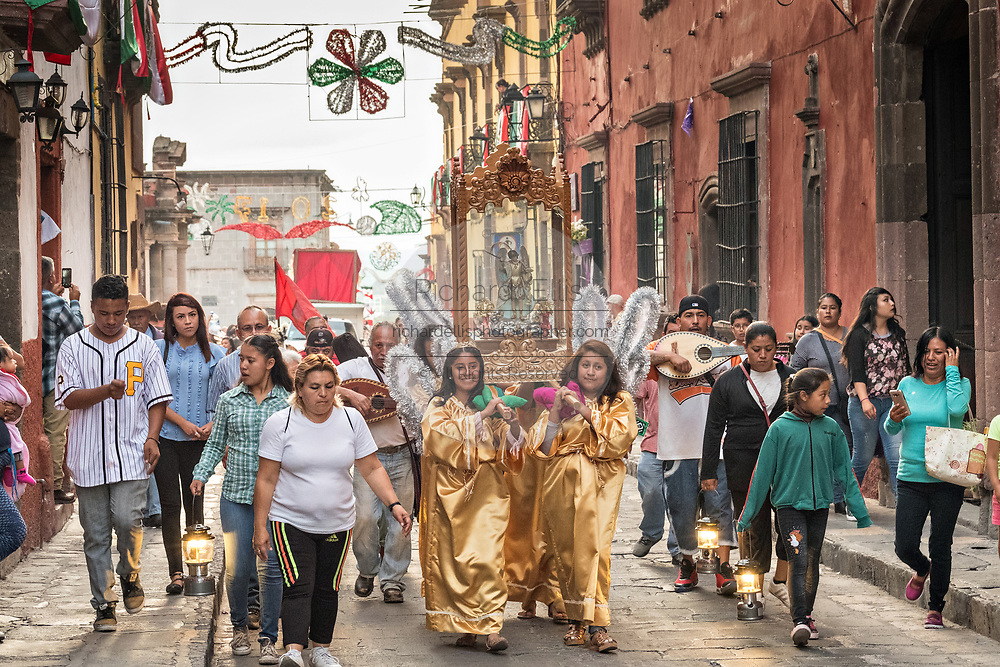 Women dressed as angels carry a statue of Saint Michael in a religious procession from the Parroquia de San Miguel Arcangel church at the start of the week long fiesta of the patron saint Saint Michael  September 21, 2017 in San Miguel de Allende, Mexico.