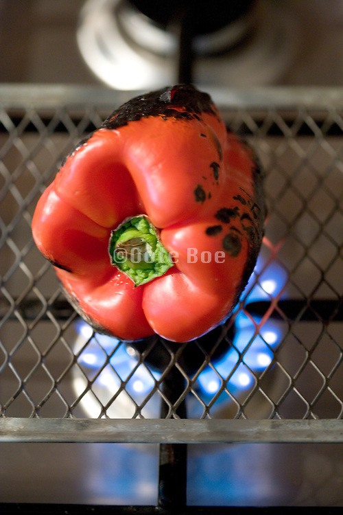 roasting a red pepper above a gas stove flame