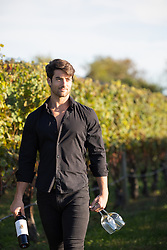 man standing in a vineyard holding a bottle of wine and two wine glasses