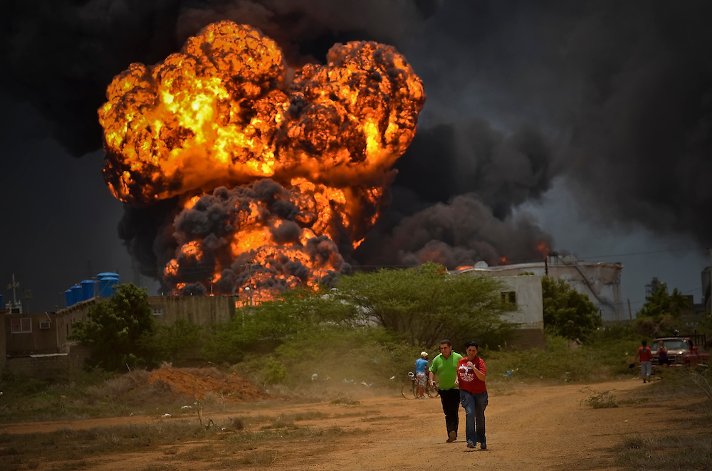 Residents of the neighborhood across the street from the Amuay oil refinery run to safety as a gasoline storage tank explodes on Monday, August 27, 2012 in Punto Fijo, Venezuela. Officials report that at least 41 people have died in the fires.