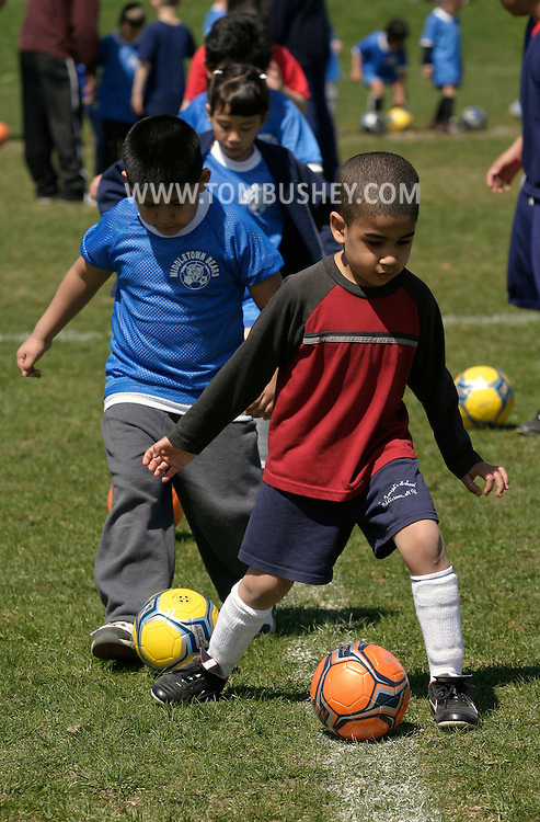 Boys and girls dribble the soccer ball during the first day of youth soccer practice at Watts Park in Middletown, N.Y. The players are first graders and second graders.April 16, 2005.