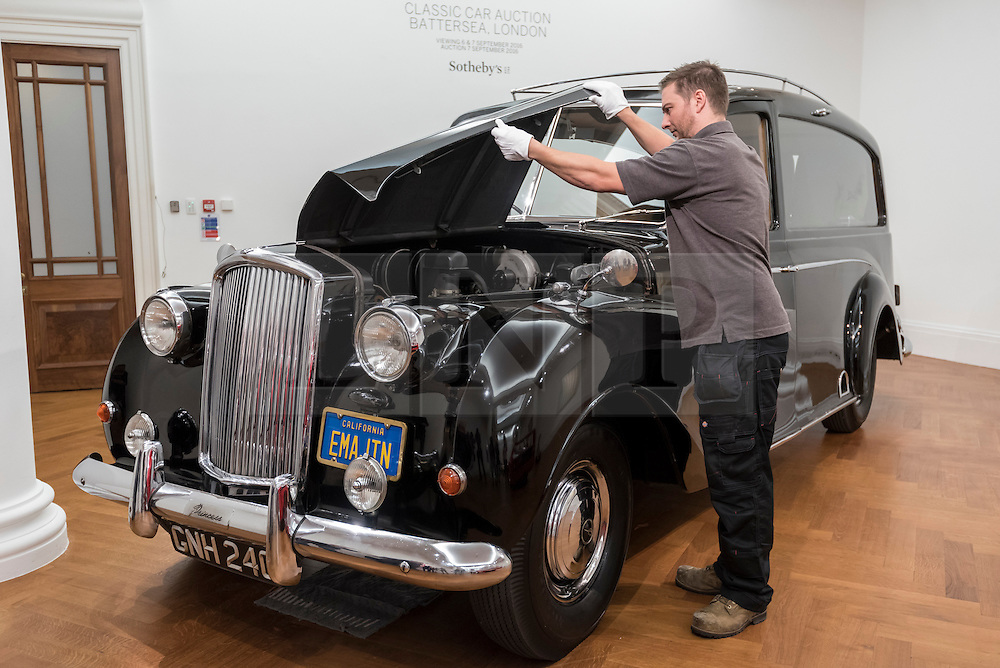 "© Licensed to London News Pictures. 12/08/2016. London, UK. A technician lifts the bonnet of John Lennon's iconic 1956 Austin Princess Limousine Hearse, immortalised in John Lennon and Yoko Ono's 1972 film ""Imagine"" (est. GBP 250,000) at the photocall for classic cars at Sotheby's, New Bond Street, ahead of their auction on 7 September in Battersea Park. Photo credit : Stephen Chung/LNP"