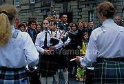 Photo of   a girl bagpiper blowing her bagpipe. without her jacket on a cold August day.  She is surrounded by a crowd  for  Edinburgh Tatoo later that evening.  The back of a girl and a woman in the same band playing the drums in the photo as well.