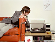 Tom, a young Mod / Indie kid, listening to music on his stereo, Southend, UK 2006