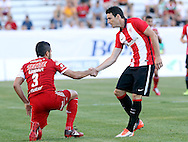 "July 18: In soccer a game outside of league play is called a ""friendly"" – but you don't always see that manifested by the players. Here, Athletic Bilbao's Aritz Aduriz helps up Club Tijuana's Javier Gandolfi in the Basque Soccer Friendly match at Albertsons Stadium in Boise, ID in July."