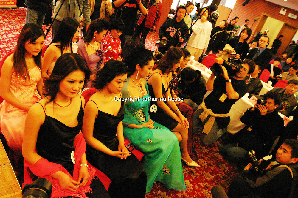 "BEIJING, 12 DECEMBER 2004:   contestants of the ""first worldwide artificial beauty pageant "" which will be held in Beijing next week, are filmed by local and foreign media during a press conference in Beijing, December 12, 2003, in China. Organizers dreamed up the pageant after Yang Yuan, , a young woman who paid USD13,000 on cosmetic surgery attemped to sue them for banning her from the finals of a traditional beauty contest last May...Beauty business in China , from cosmetic surgeries to hair brush sales, has amounted to more than USD 7 billion in 2003..."