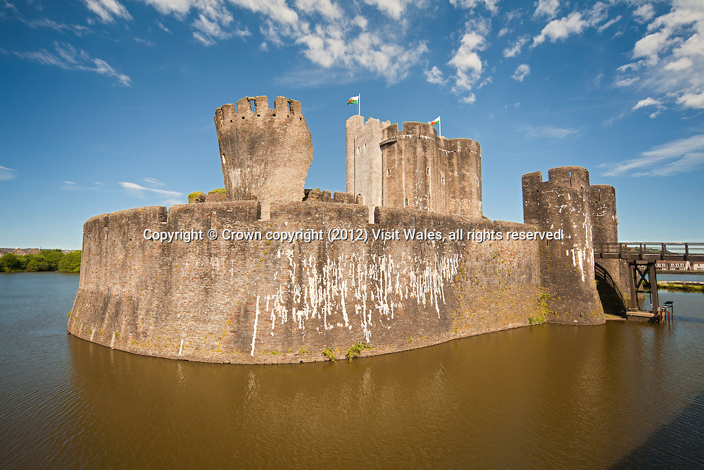 View across lake from Outer Ward to south east (leaning) tower and Inner Ward <br /> Caerphilly Castle <br /> Cadw Sites<br /> SAMN: GM002<br /> NGR: ST155870<br /> Caerphilly<br /> South<br /> Castles<br /> Medieval<br /> Defence<br /> Historic Sites