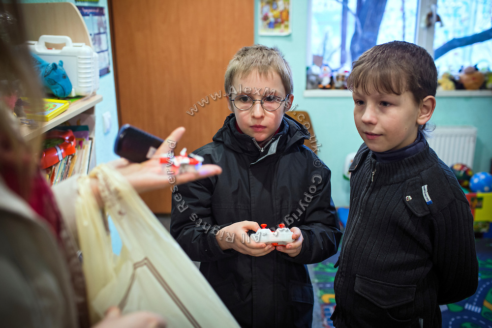 With his mother Olga, 36, Yeroslav, 10, (centre) is showing his photo/video-recording drone to a young friend inside a community meeting place in support of internally displaced persons. (IDPs) Yeroslav is taking part to the UNICEF-sponsored One Minute Junior project for internally displaced persons (IDPs), carried out by the local NGO 'Ukrainian Frontiers' in the city of Kharkiv, the country's second-largest, in the east. The conflict between Ukrainian army and Russia-backed separatists nearby, in the Donbass region, have left more than 10000 dead since April 2014, including over 1000 since the shaky Minsk II ceasefire came into effect in February 2015. The approximate number of people displaced by the conflict is 1.4 million as of August 2015. Yeroslav's mother, Olga, is also a participant to a different project of 'Ukrainian Frontiers', called 'Self-Employment', first as a beneficiary, and now as a paid hotline coordinator for people seeking jobs and formation courses.