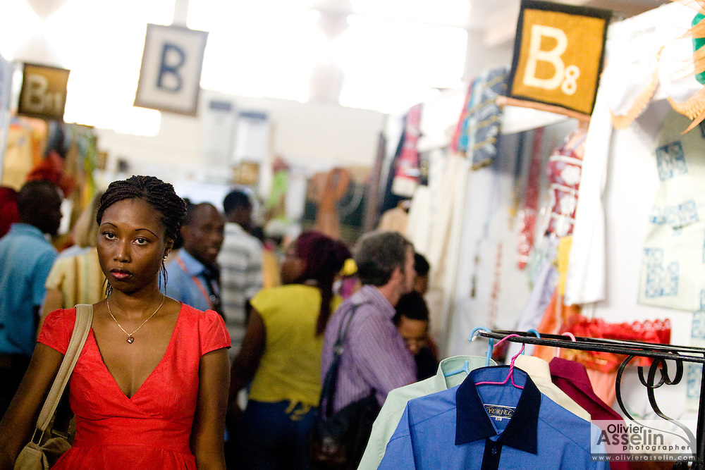 A woman in a red dress walks through alleys in a pavilion at the 22nd Salon International de l'Artisanat de Ouagadougou (SIAO) in Ouagadougou, Burkina Faso on Saturday November 1, 2008.
