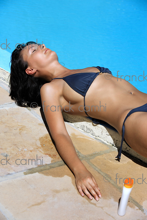 young beautiful caucasian brunette woman relaxing or sleeping near a swimming pool getting tanned by the sun with sunblock cream product on the side