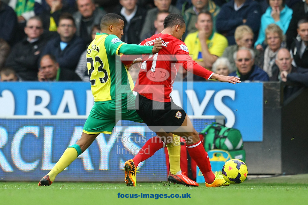 Picture by Paul Chesterton/Focus Images Ltd +44 7904 640267<br /> Martin Olssen of Norwich and Peter Odemwingie of Cardiff in action during the Barclays Premier League match at Carrow Road, Norwich.
