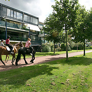 Nederland Rotterdam Deelgemeente prins alexander 08-09-2008 20080908 Foto: David Rozing ..Prinsenland, meiden rijden paard op fietspad in woonwijk .horseback riding .Deelgemeente Prins Alexander is het op 1 na diepst / laag gelegen gebied in Nederland, het laagste punt in de deelgemeent is  6,67 meter beneden NAP. Prins Alexander, second deepest area in the Netherlands, deepest point in this area, below sealevel: - 6,67m NAP...Foto: David Rozing
