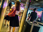 02 FEBRUARY 2015 - BANGKOK, THAILAND: A university student walks through metal detector at a security checkpoint while the guard (right) ignores people coming in at Siam Discovery, a high end shopping mall in central Bangkok. Government sources are saying that security has been heightened following two small bomb attacks close to Siam Paragon, a nearby mall. One person received minor injuries in the attack and a couple of windows were blown out. After months of relative calm following the May 2014 coup, tensions are increasing in Bangkok. The military backed junta has threatened to crack down on anyone who opposes the government. Relations with the United States have deteriorated after Daniel Russel, the US Assistant Secretary of State for Asian and Pacific Affairs, said that normalization of relations between Thailand and the US would depend on the restoration of a credible democratically elected government in Thailand.        PHOTO BY JACK KURTZ