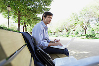 Businessman using laptop on park bench