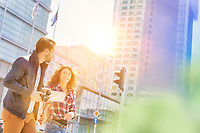 Portrait of young attractive couple walking in the middle of the city with lens flare in background