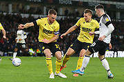 *Derby County forward Tom Lawrence (10) crosses the ball under pressure from Millwall defender Alex Pearce (15) during the EFL Sky Bet Championship match between Derby County and Millwall at the Pride Park, Derby, England on 14 December 2019.