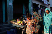 A young girl and other women are walking near a fruit vendor on the roads of Madiyaw colony, Lucknow District, Uttar Pradesh.