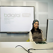 "Barcelona, Spain. Inside Barcelona digital technology centre. A girl show the latest AI project, called ""Brainable""  developed by Bdigital researchers team. The European Union R&D project Brainable aims to enhance individual indipendence and reduce the social limitations of people with physical disabilities, raising the possibility for them to interact with their surroundings through the design of Person - Computer interfaces formed by sensors that gauge the user's physical and emotional state - especially through brain computer interfaces (BCIs) - and individual environment."