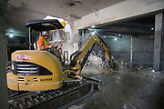 A small excavator fitted with a jackhammer breaks through the outer wall of the Union Square Garage, opening it up to the north station concourse.