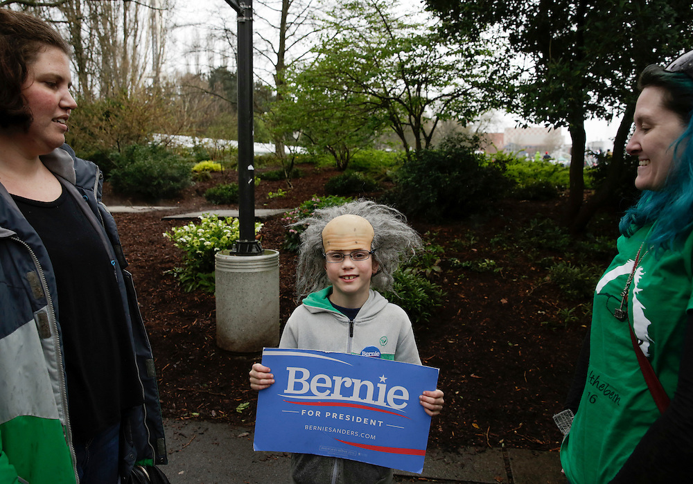 Sam Moore, 8, of Oak Harbor, Wash. waits in line with his mother, Sarah Moore (L), and family friend Fe Mischo, to attend a rally for Democratic presidential candidate Bernie Sanders at Key Arena on March 20, 2016 in Seattle.  AFP PHOTO/JASON REDMOND