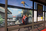 Local community passes a hoarding showing aspiration and consumerism of nearby Westfield City shopping complex, Stratford