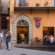 Men chat on corner and friends sit around table on outside deck of Aries Cafe Gelateria in the piazza Garibaldi in the Umbrian hilltown of Montone Italy