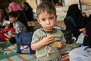 A child eats some biscuits at a reception centre near Badush shortly after fleeing the recently liberated western Mosul 17 Tammuz neighbourhood on May 19, 2017.