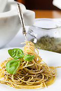 Vertical shot of plate with spaghetti dressed with pesto sauce and decorated with basil leaves.
