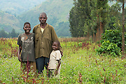 """Shasha, DRC -   2014-08-29 - Human interest story 3. Father Jean Nzabimana walks with his two sons Tuizere, 8, and Zakayo, 13, in Shasha, DRC on August 29, 2014. Both boys had club feet on both limbs, explains Jean, a widowed farmer with seven children. """"I was angry at nature. I just prayed to God, 'please perform a miracle.' Then it was like from Heaven, when I got the message that they were doing surgeries at Kirotshe. I have no means but CBM through HEAL Africa was able to do this for my children. I am very grateful."""" After receiving surgery three months earlier in June 2014 at Kirotshe Medical Centre mobile clinic IA2014, both boys are no longer ridiculed or stigmatized. """"I'm the happiest among men,"""" says Jean.  Photo by Daniel Hayduk"""