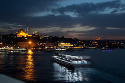 The buzzing traffic of the ferrys just by the Galata Bridge in the waters of the golden horn and majestic in the distance stands the Suleymaniye Mosque, Istanbul, Turkey, September 15, 2012. Photo by Silvia Baron / i-Images.