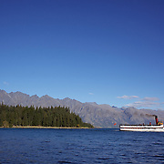 The TSS Earnslaw,  a 1912 Edwardian vintage twin screw steamer on the waters of Lake Wakatipu in, Queenstown, New Zealand. .It is one of the oldest tourist attractions in Central Otago, and the only remaining passenger-carrying coal-fired steamship in the southern hemisphere..The TSS Earnslaw heads along Lake Wakatipu from Queenstown  daily, running tourist trips to Walter Peak Station passing magnificent  peaks and contrasting shoreline foliage along the lakeside. Queenstown, New Zealand. 19th March 2011. Photo Tim Clayton