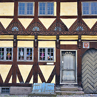 Østerbye's Farm House in Odense, Denmark<br /> This yellow half-timbered building dates back to 1631. Notice the emblems above the large door. On the left are the initials CR which stands for the original, 17th century owner Christen Rasmussen. The monogram on the right represents his wife. In 1857 it became the Osterbyes Gård or farm house. Since 1947, this historic complex on Sortebrødre Torv has been part of the Møntergården Museum.