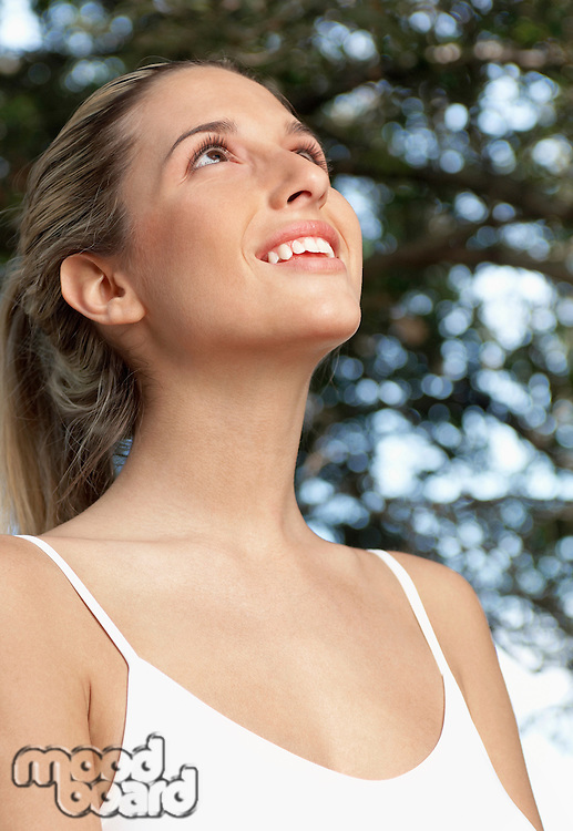 Young woman looking up and smiling portrait low angle view