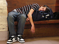 PHILADELPHIA - MAY 25: Andrew Michael, who had been waiting for hours, takes a nap as he waits for a train at 30th Street Station May 25, 2006 in Philadelphia, Pennsylvania. Thousands of Amtrak passengers were starnded from Washington, D.C. to New York during a power outage along the East Corridor. (Photo by William Thomas Cain/Getty Images)