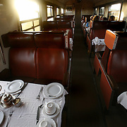 "Passengers eat breakfast in the dining car of the Nairobi-Mombasa train as the sun comes up. The approximately 300 mile journey took 16 hours this trip. Also known as the ""Lunatic Express"", It was the railway line that built Kenya, linking the port town of Mombasa.through the capital, Nairobi, to the shores of Lake Victoria and on to the.Ugandan capital, Kampala. It cost $5m (in 1894 money) and countless workers died during its construction. There were derailments, collisions, tribal raids and attacks by lions. Yet despite becoming one of Kenya's national treasures and a vital economic artery for east Africa, the railway now lies in a state of disrepair. A South African consortium has taken it over and plans to invest millions, returning it to its former glory. But there has been a row over the railway's financing which may yet derail the .project. .."